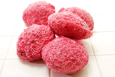 lamington: A collection of round pink lamington snowballs frosted with cocnut on an isolated white studio background