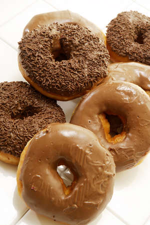 A collective pile of various types of chocolate frosted donuts on an isolated studio background photo