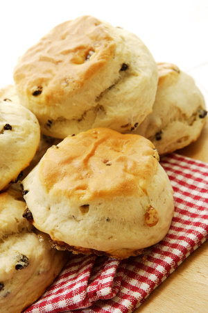 A closeup of a pile of freshly baked scones or biscuits on a checkered red cloth on a wooden cutting board