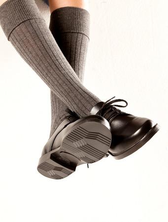 pieds sales: Un ensemble balan�ant des jambes d'enfants avec de longues chaussettes grises et des chaussures scolaires noir sur un fond blanc