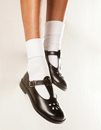 zapatos escolares: Un conjunto colgando de las patas de los ni�os con calcetines blancos cortos y zapatos de la escuela las ni�as negro sobre un fondo blanco