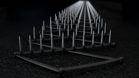 A sharp spike strip spread over dark wet tarmac