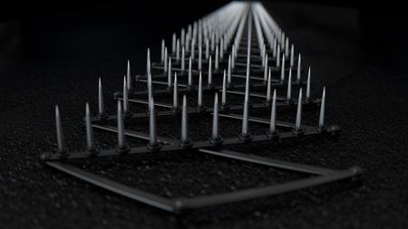 road rage: A sharp spike strip spread over dark wet tarmac
