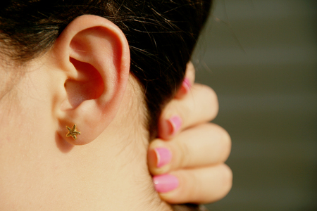 earing: side view of female person holding hair to side with pink nail polished fingers showing starfish earing on ear