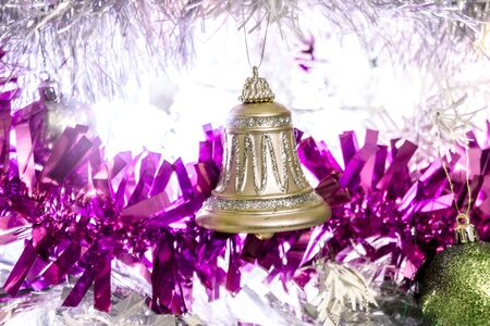 A gold glittery bell on w white christmas tree covered in purple tinsil