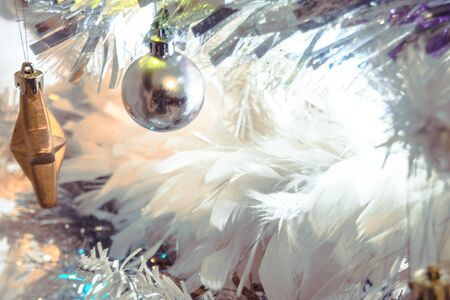 a festive and modern white christmas tree with feathers, tinsil,lights and bulbs