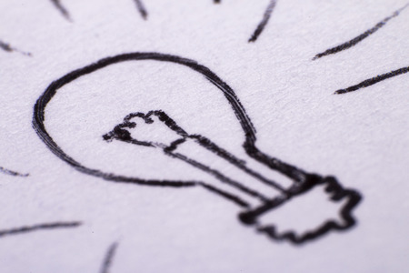 a pen drawing of a lightbulb on paper close up, a symbol of an idea or putting it to paper