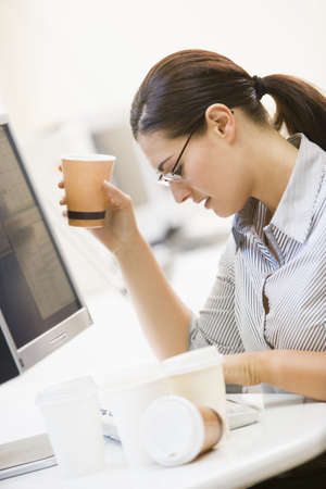 Female Office Worker At Desk Drinking Coffee photo