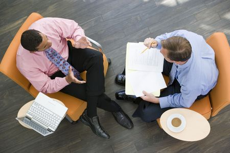 overhead view: Overhead View Of Two Businessmen Having Meeting In Office Lobby