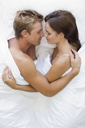 couple cuddling: Overhead View Of Young Couple In Bed  Stock Photo