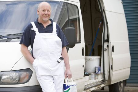 leaning on the truck: Decorator Standing Next To White Van