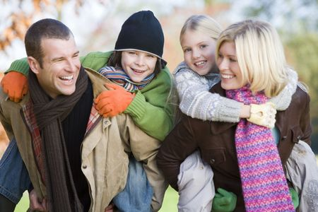 Parents outdoors piggybacking two young children and smiling  photo