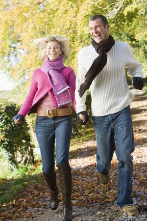Couple running outdoors on path in park smiling photo