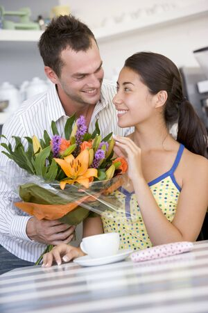 Man giving woman bouquet of flowers photo