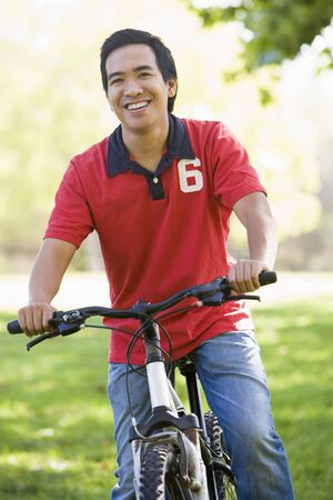 Asian man riding bike in park photo