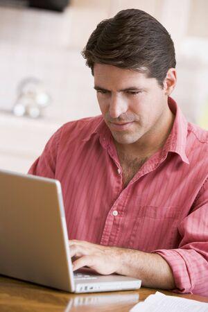 Hispanic man using laptop at home Stock Photo - 2901547