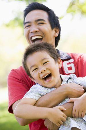 亚裔父亲和儿子在公园玩乐趣