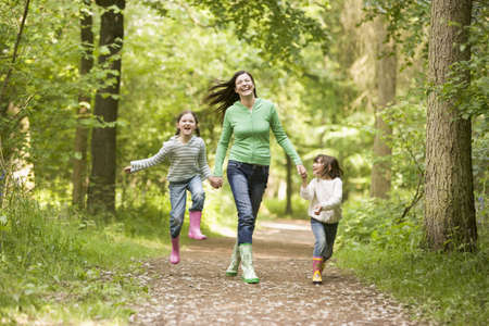 Mother running along woodland path with 2 childrren photo