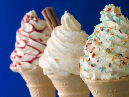 helados con palito: Conos azotados del helado con tres diversos toppings Foto de archivo