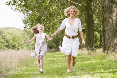 Mother and daughter running on woodland path photo