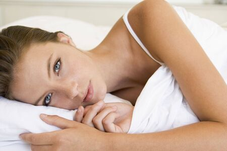 Young woman laying bed photo