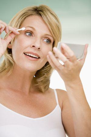 Woman putting on eye make up photo
