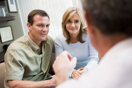 Couple in consultation at IVF clinic talking to doctor photo
