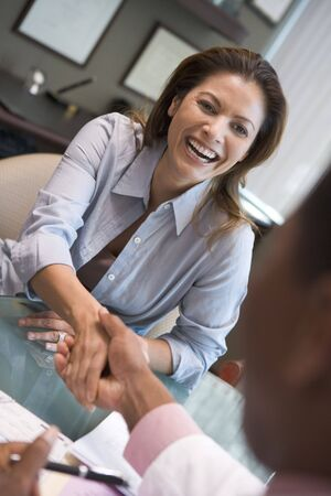 Woman sitting at desk shaking doctor's hand at IVF clinic Stock Photo - 2955504