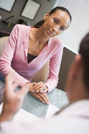 Woman having meeting with doctor in IVF clinic sitting at desk Stock Photo - 2955500