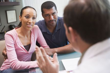Couple having discussion with doctor in IVF clinic sitting at desk Stock Photo - 2955506