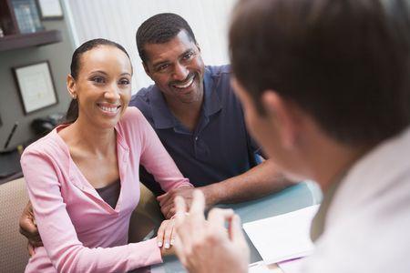 Pareja en la discusión con médico en la clínica FIV sesión en escritorio  Foto de archivo