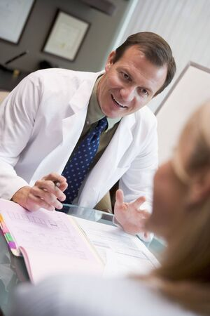 Doctor in consultation with female patient sitting at desk Stock Photo - 2955498