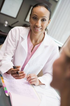 Woman in discussion with patient in IVF clinic seated at desk Stock Photo - 2955494