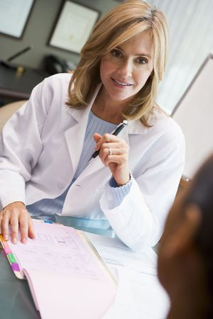 Woman in discussion with patient in IVF clinic seated at desk photo