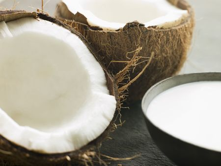 noone: Dish of Coconut Milk with a Split Fresh Coconut Stock Photo