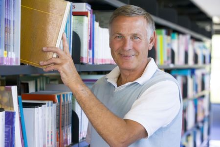 baby boomer: Man in library pulling book off a shelf (depth of field)