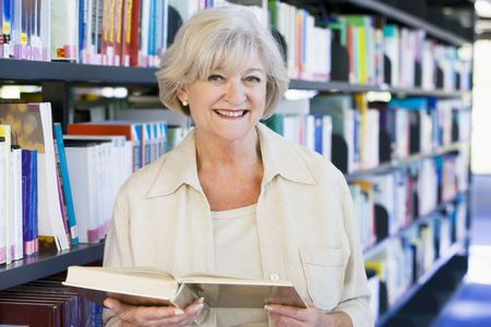 colo: Woman in library holding book (depth of field)