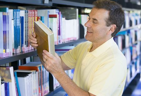 caucasian appearance: Man in library looking at book (depth of field)