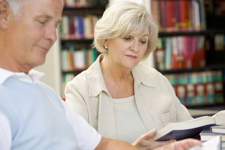 caucasian appearance: Man and woman in library reading (selective focus)