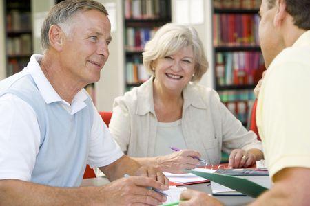 Drie mensen in de bibliotheek schrijven in notebooks (selectieve aandacht)