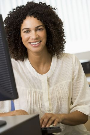 computer terminal: Woman sitting at a computer terminal typing (high key)