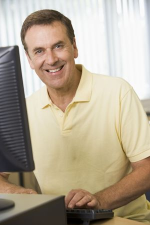 boomers: Man sitting at a computer terminal typing (high key)