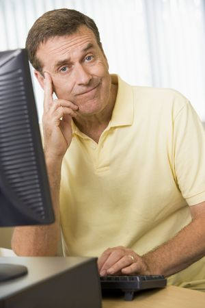 ambivalence: Man sitting at a computer terminal bored (high key)