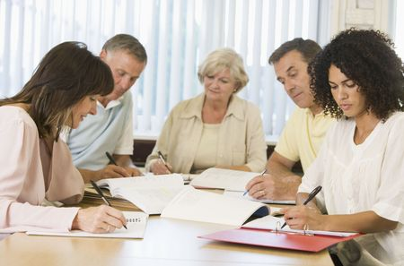 70s adult: Five adult students studying at table (depth of field) Stock Photo