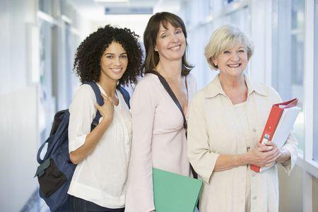 Tre donne in piedi in corridoio con libri (chiave alta)
