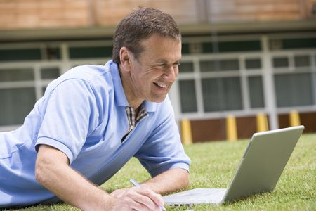 baby boomer: Man lying on lawn of school with laptop