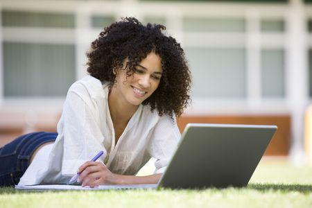 Frau liegend auf Rasen Schule mit Laptop
