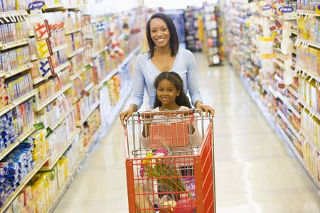 aisles: Mother with young daughter shopping at the grocery store.