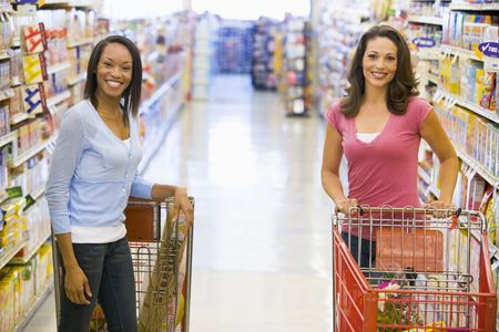 Two women talking to each other at a grocery store