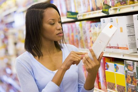 checking ingredients: Woman shopping at a grocery store